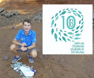 Oliver Baker on a beach with plastic that he has gathered up