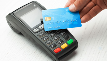 Debit card being held up to a debit machine