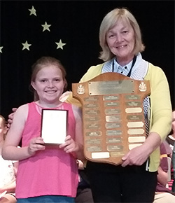Avery accepting her award on stage with her teacher
