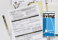 Documents and unfilled forms on a table with a pen and logo for Independent Living Nova Scotia