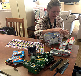 A student sits at a table assembling a hygiene kit.